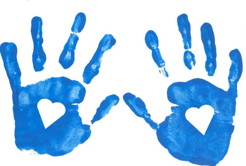 Picture of open Hand prints in blue finger paint with hearts cut out of the palms